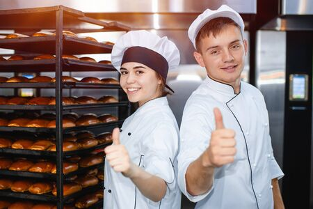Young guy and girl bakers on the background of an industrial oven in a bakery show thumb up.