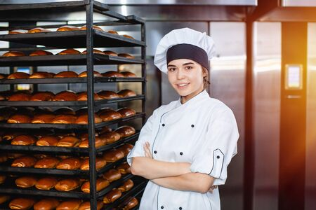 Portrait of a young baker girl on the background of an industrial oven with pastries in a bakery. Stok Fotoğraf