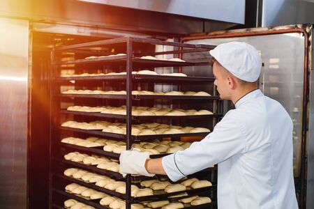 a baker carries a cart with a baking tray with raw dough into a baking oven. industrial oven in a bakery. Stok Fotoğraf
