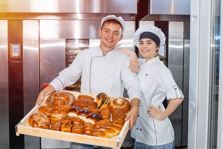 Bakers man and girl with a full box of hot pastries in their hands ha the background of an industrial oven in a bakery.