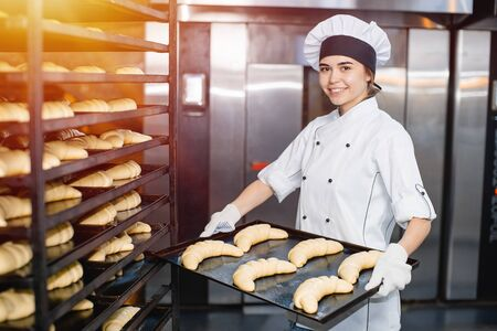 Baker girl with a baking sheet with raw dough in hands on the background of an industrial oven in a bakery