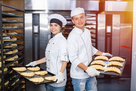 baker boy and girl with baking sheets with raw dough on the background of an industrial oven in a bakery. Stok Fotoğraf