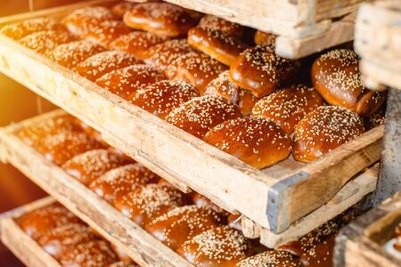 Wooden shelves with fresh pastries in a bakery. Sesame Buns.