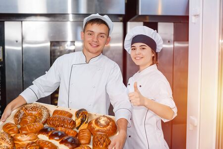 Bakers man and girl with a full box of hot pastries in their hands on the background of an industrial oven in a bakery. thumb up.