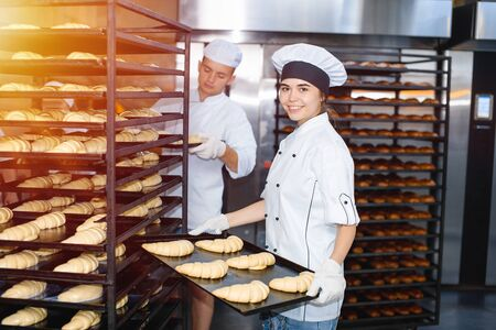Baker girl with a baking sheet with raw dough in hands on the background of an industrial oven in a bakery.
