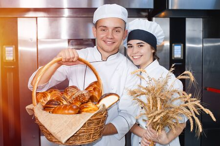 bakers boy and girl with a baking basket and spikelets of wheat against the background of an industrial oven in a bakery.