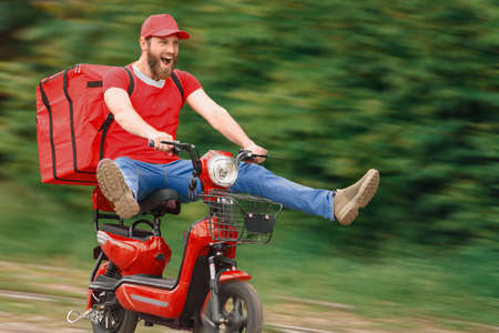 A food delivery man on a red moped with a food delivery bag flies at high speed with his legs spread out to the sides.