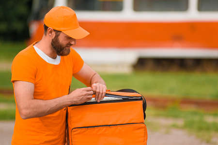 Food delivery man in orange uniform opens a food delivery bag.