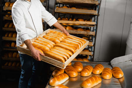 The baker holds a wooden box with hot bread on the background of shelves with bread in the bakery. Industrial bread production Zdjęcie Seryjne