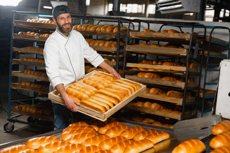 The baker holds a wooden box with hot bread on the background of shelves with bread in the bakery. Industrial bread production Banco de Imagens