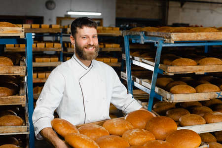 A baker holds a tray with fresh hot bread in his hands against the background of shelves with fresh bread in a bakery. Industrial bread production