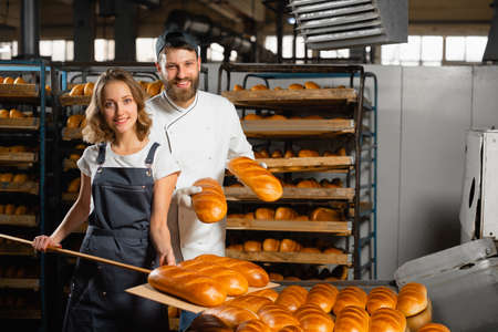 Young bakers with a wooden shovel with bread in their hands against the background of shelving with bread in a bakery. Industrial bread production