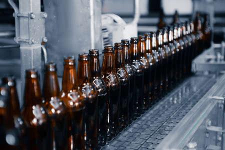 Glass beer bottles of brown color on the conveyor line of beer bottling close up