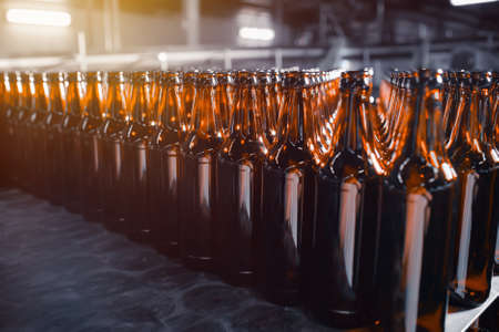 Rows of glass beer bottles of brown color close up on the stack