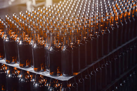Rows of brown glass beer bottles on the stack Banco de Imagens
