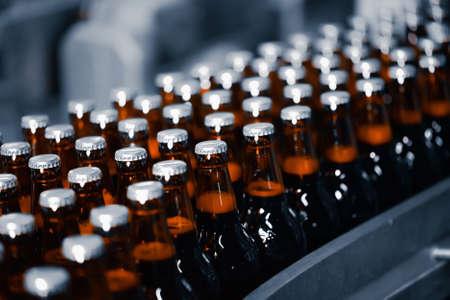 Beer bottles on a conveyor belt. Industrial beer production