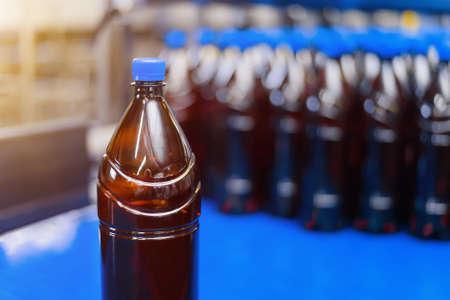 Plastic brown beer bottle on conveyor belt close up
