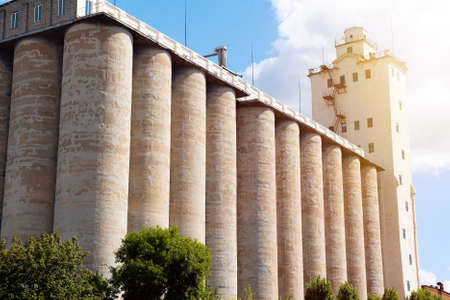 Concrete elevator, grain tank on a sunny sky background Banco de Imagens