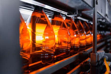 Plastic brown beer bottles on a conveyor belt close-up. Production of plastic bottles. Banco de Imagens