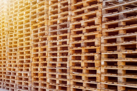 Wooden Euro pallets stacked in big industrial storehouse
