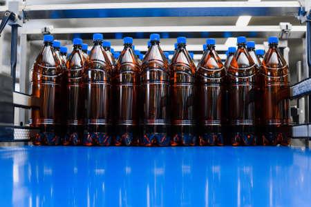 A row of plastic beer bottles on a conveyor belt. Industrial production of beer. Beer bottles mockup Banco de Imagens