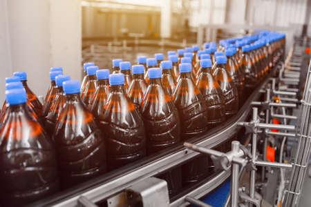 Row of brown beer plastic bottles on beer filling conveyor line