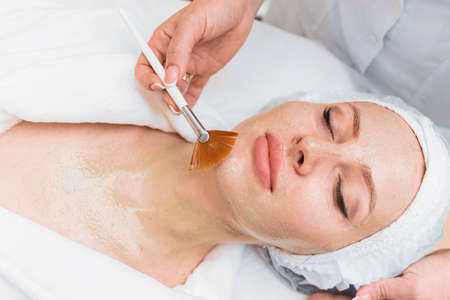 Brush applies an enzyme mask to a woman's face.