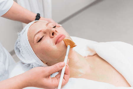 Brush application of an enzyme mask to a woman's face.