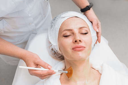 Application of an enzyme mask with a brush on a woman's face top view.