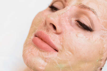 Enzyme mask in the process of drying on a woman's face close-up. Rejuvenation and facelift in cosmetology.