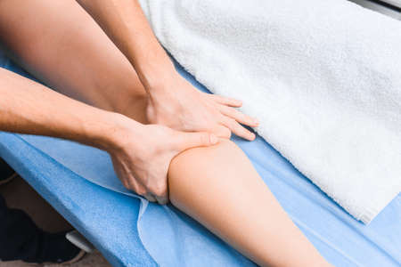 Top view of anti-cellulite massage of the gastrocnemius muscle. Hands of masseur close up.