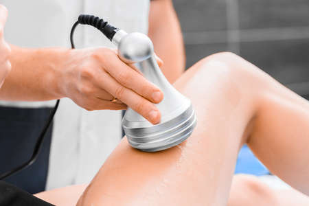 Anti-cellulite massage with an ultrasound device close-up. Hardware rejuvenation of the body.