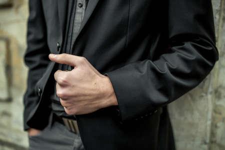 lapel: Close-up of unrecognizable man holding his jacket lapel