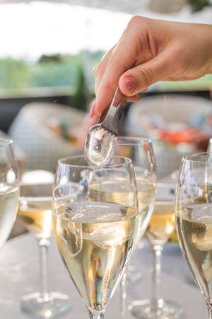 The waiter throws a ice peaces in wine glasses using tongs, Gray table covered with half full glasses. Glasses of white wine for party or wedding.