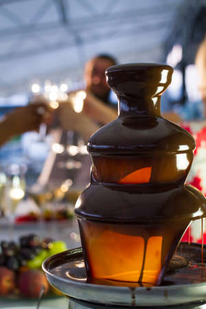 Foreground focus on dripping chocolate from fondue pot with wine glasses and fruit in background