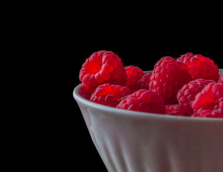 Side view on handful of ripe and fresh raspberries in white porcelain cup against black background