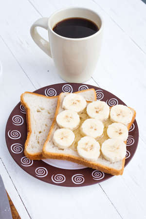 banana bread: Close-up of breakfast with two sandwiches with honey and banana and cup of black coffee on table Stock Photo