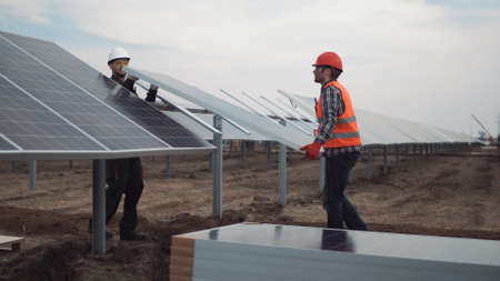 Two builders workers mounting the panels for the solar energy using.