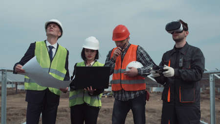Man controlling the drone in virtual reality goggles while managers discussing the plan of the field with solar panels using computer laptop on solar farm Banque d'images