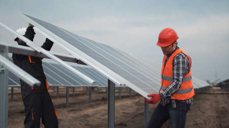Two workers in a uniform and hardhat install photovoltaic panels on a metal basis on a solar farm Standard-Bild