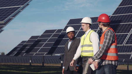 Three mixed ethnic men in uniform and hard hat walking around solar power station and examining it. Side view
