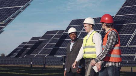 Drie gemengde etnische mannen in uniform en bouwvakker wandelen rond zonne-energiecentrale en de behandeling ervan. Zijaanzicht Stockfoto