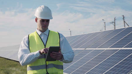 Technician walks beside array of solar panels while wearing hard hat and holds computer digital tablet Zdjęcie Seryjne