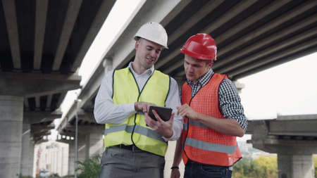4K shot of Two young workers in red and yellow vests and hard hats lookig at tablet computer and discusses a project while standing under the bridge construction. Movement stabilized Banque d'images