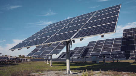 Multiple sets of large solar panel arrays facing upward to a deep blue sky from ground