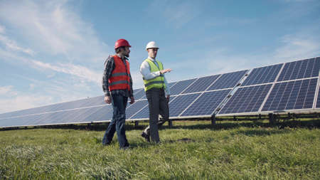 Two male electrician workers in reflective vests and hard hats walking in between long rows of photovoltaic solar panels and talking about installation of new solar panels.