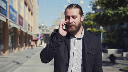 4K Handsome smiling bearded man walking along city street, talking cell phone simultaneously.