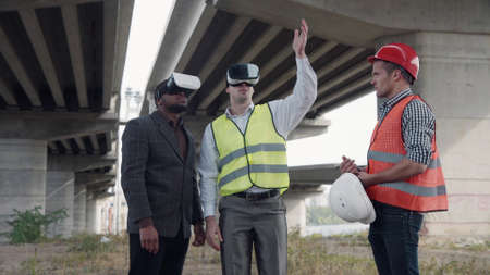 4K shot of business team of two architects and afro american foreman in suit uses virtual reality glasses to discuss a project of development while standing under overpass construction. Standard-Bild