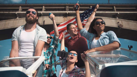 independance: Emotional group of mixed ethnic young friends on board a motor boat as they approach a bridge along a river laughing and cheering waving their beers in the air. Celebrate an Independence Day on July 4 Stock Photo