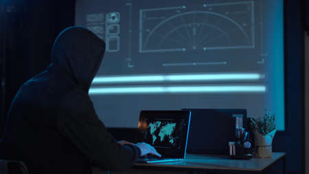 Man in the hood from his back sitting and working at laptop as hacker, with world map on wall in background. Then he take off usb flash disk and run away. Perhaps he has stolen information or has cracked system and has loaded a virus.